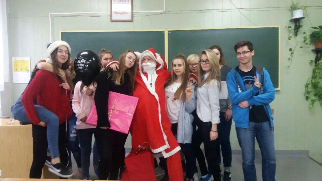 Uczniowie świętują Mikołajki. Niektórzy przebrani: 1 osoba w stroju Mikołaja, są też czapki mikołajkowe, prezenty, balony